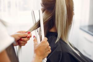 Mulher mexendo no cabelo de outra mulher