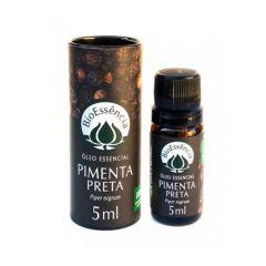 fundo branco e oleo essencial de bio essencia ao centro. embalagem cilindrica de papel, com foto de pimenta. ao lado, um vidro âmbar de óleo essencial de pimenta preta